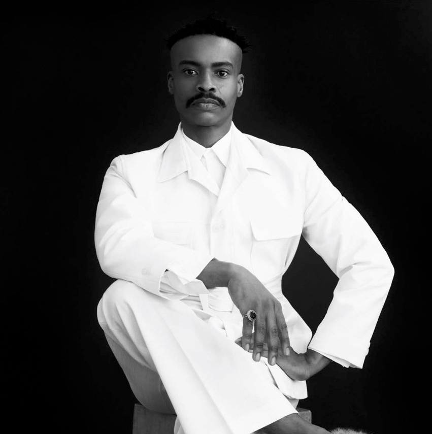 black and whote portrait of artist Athi Patra Ruga, seated in a white suit. Photo: Jarrad Figgins.