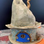 A small ceramic house with a crooked chimney and bright blue door