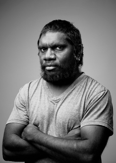 Portrait of artist Curtis Taylor. Curtis is staring into the camera with his arms crossed.