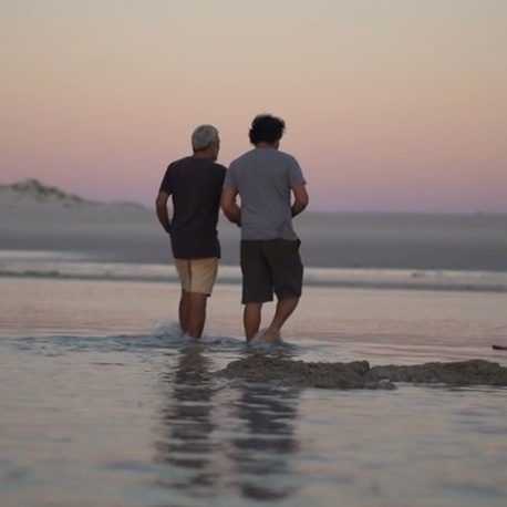 two men in shorts and tshirts walking away from us in the shallows of the ocean at sunset