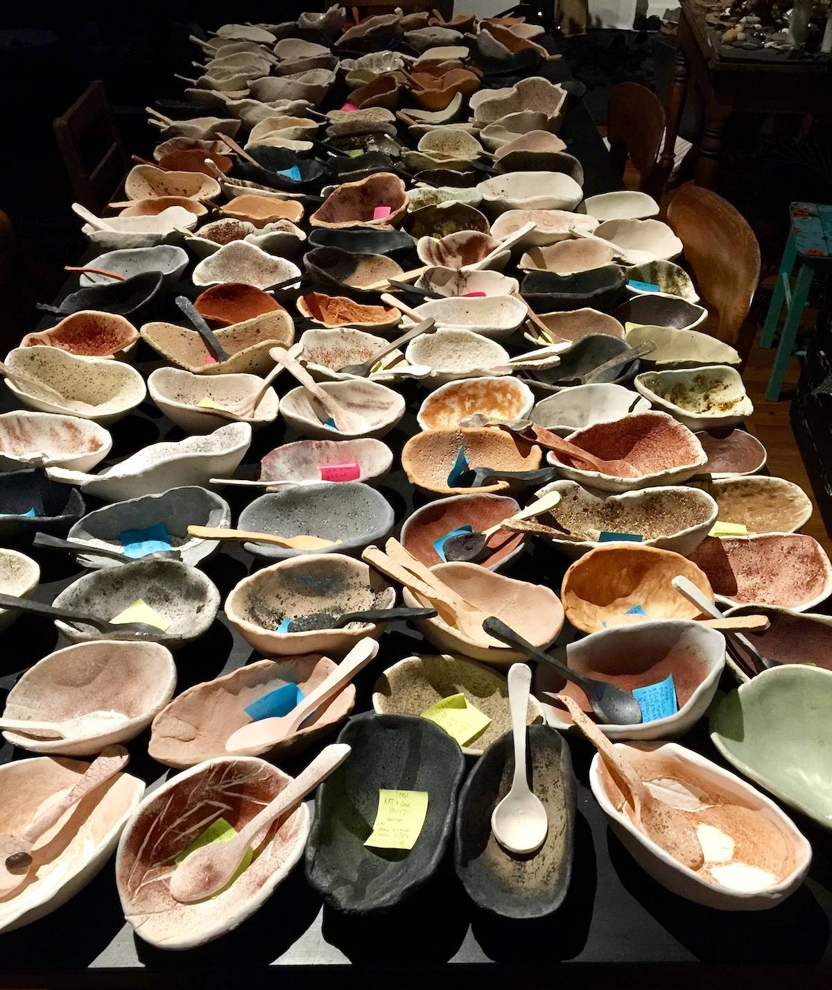 Various bowls with spoons and a note inside them all crammed onto one table