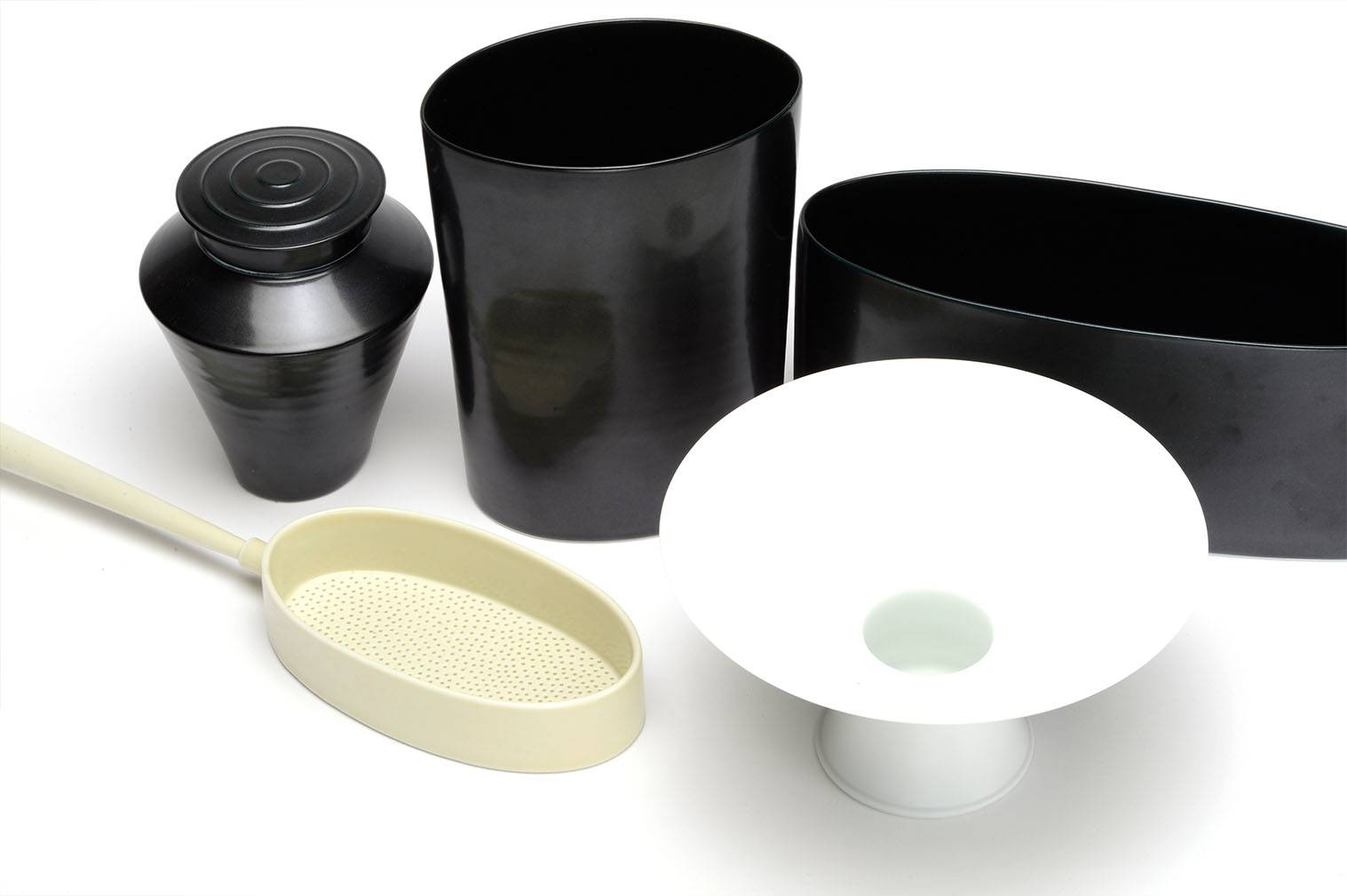 Porcelain black tea caddy, black oval forms, yellow sieve and white bowl.