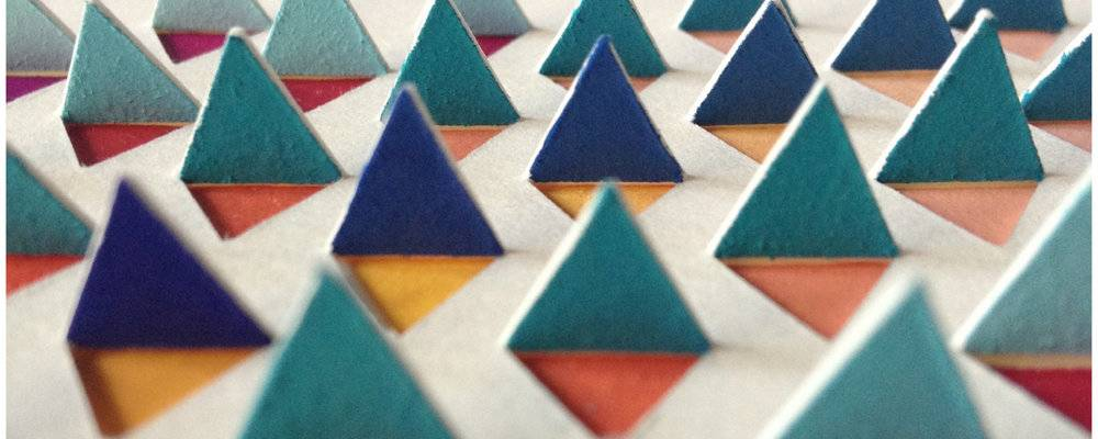 Paper triangles cut out to reveal more coloured triangles