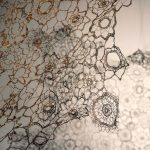 Crochet copper wire patterns with shadows behind