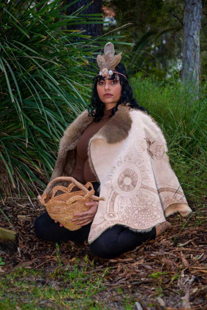 Model wears fashion cloak in woods